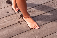 Bare feet of a girl walking on a wooden pier Royalty Free Stock Photo