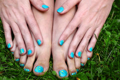 Bare feet and hands with manicure pedicure. Bare feet and hands with creative teens manicure and pedicure on the green grass lawn background Royalty Free Stock Photography