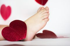 Bare feet among hearts. Valentine's day card with bare feet among red hearts royalty free stock images