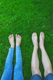 Bare feet and legs in grass stock image