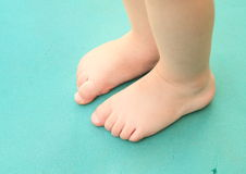 Bare feet of little baby. Bare feet of a little baby - girl or boy standing on green sleeping pad stock image