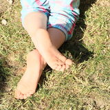 Bare feet of a little girl. Little girl with bare feet on grass stock photos