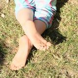 Bare feet of a little girl Stock Photos