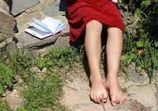 Bare feet of a little girl with a notebook. Little girl with bare feet and red skirt Stock Photo