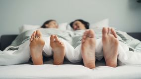 Bare feet male and female moving in bed under blanket in funny dance. Bare feet male and female are moving in bed under clean white blanket in funny dance rhythm stock footage