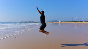 Bare feet Man jumping on beach with waves Stock Image