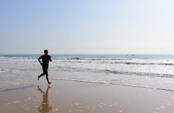 Bare feet Man running on beach with waves Royalty Free Stock Images