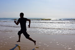 Bare feet Man running on beach with waves and reflection. Stock Images