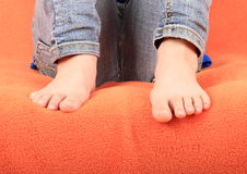 Bare feet on orange cover. Bare feet of a little girl - child sitting on sofa with orange cover Royalty Free Stock Images
