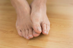 Bare feet on parquet floor Stock Photos