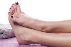 Bare feet with pedicure propped by towel. On soft purple treatment table against white background royalty free stock photography