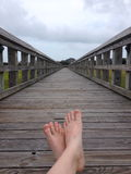 Bare feet on a pier Stock Images