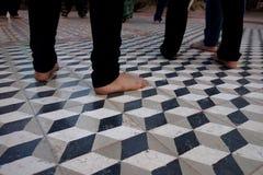 Bare Feet of Pilgrims on Tile Floor Stock Photos