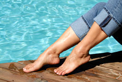 Bare Feet by the Pool. A woman's bare feet by the edge of a swimming pool Royalty Free Stock Images