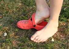 Bare feet putting on shoe. Bare feet of a little kid - girl putting on her shoe on grass of meadow Royalty Free Stock Photos