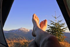 Bare feet resting camper in tent with mountain view Stock Photos