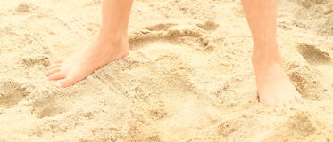Bare feet on sand. Bare feet of a little girl - child standing on sand royalty free stock photo