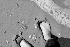 Bare feet on sandy shore - black and white Royalty Free Stock Photo