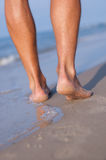 Bare feet at the sea. Closeup of man's feet at the shore Royalty Free Stock Images