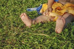 Bare feet of a small child sitting. On green grass Stock Images