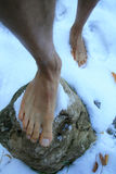 Bare Feet In Snow. Man steps with bare feet on a rock in the snow Royalty Free Stock Photos