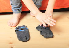 Bare feet and socks. Bare feet of a girl - young kid standing by socks on wooden floor ready to dress up Royalty Free Stock Photo