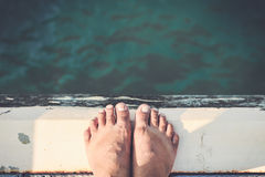 Bare Feet Standing on Cement Edge Stock Photo
