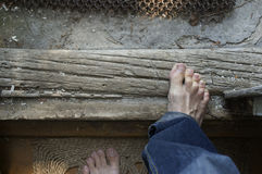 Bare Feet And Threshold. Male bare feet stepping out of the house, overhead indoor shot royalty free stock photos