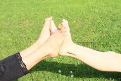 Bare feet of two little kids. Little girl leaning with her bare feet with yellow blossom to bare feet of a little boy Stock Photo