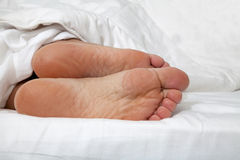 Bare feet under duvet Stock Photos