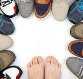 Bare feet on white. Sneakers around isolated Royalty Free Stock Photography
