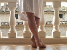 Bare feet of woman in bathrobe at balcony railing Stock Photos