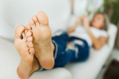 Bare feet of woman in jeans using smart phone.bare foot. Bare feet of woman in jeans using smart phone lying on white sofa royalty free stock photos