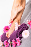 Bare feet of a woman surrounded by flowers Stock Photo