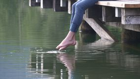 Bare feet of woman touching water. Summer refreshment. Girl's bare feet swinging over the water dipping toes stock video