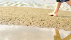Bare feet of woman walking slowly on sand on the shore.  stock footage