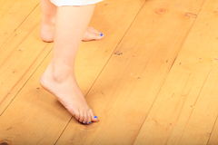 Bare feet on wooden floor. Bare feet with blue nails of a girl - young woman standing on wooden floor royalty free stock photo