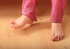 Bare feet on wooden floor. Bare feet a girl - young kid standing and stepping on wooden floor Stock Photography