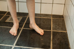 Bare Feet of a Young Boy Inside a Home Bathroom. Bare Feet of a Young Boy Stepping on the Floor with Water Inside the Home Bathroom Stock Image
