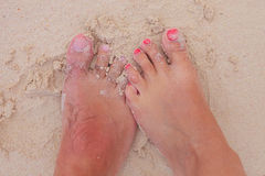 Bare feet of a young couple in wet sand Royalty Free Stock Image