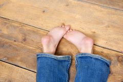 Bare feet of a young girl wearing jeans Royalty Free Stock Images