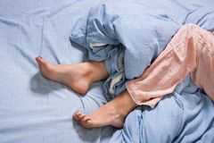 Bare Feet of a Young Woman on Blue Bed Royalty Free Stock Photos
