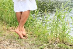 Bare feet on grass by water. Bare feet of young woman - girl standing on bank of river Royalty Free Stock Images