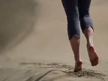 Bare feet of young woman jogging/walking on the beach. At sunrise Royalty Free Stock Image