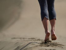 Bare feet of young woman jogging/walking on the beach. At sunrise Stock Image