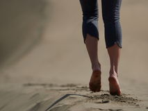Bare feet of young woman jogging/walking on the beach Stock Image