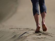 Bare feet of young woman jogging/walking on the beach. At sunrise Stock Photos