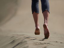 Bare feet of young woman jogging/walking on the beach at sunrise Stock Photos