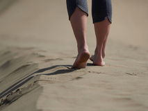 Bare feet of young woman jogging/walking on the beach at sunrise Stock Images