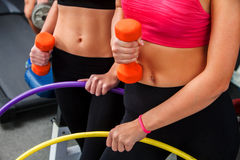 Bare female belly with dumbbells and hoop at gym. stock images
